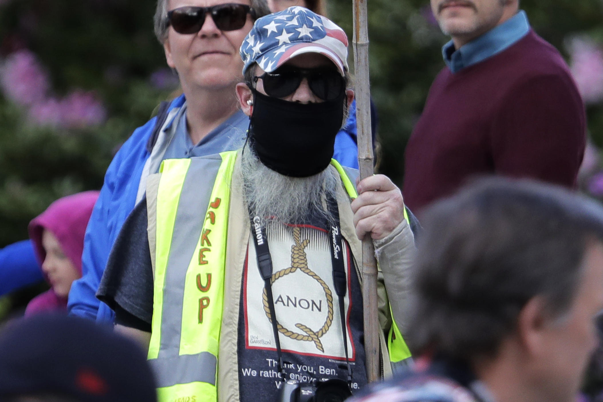 In this May 14, 2020, photo, a person carrying a sign supporting QAnon wears a t-shirt that shows the QAnon name in the format of a rope noose during a protest rally in Olympia, Wash., held against Gov. Jay Inslee and Washington state stay-at-home orders made in efforts to prevent the spread of the coronavirus.