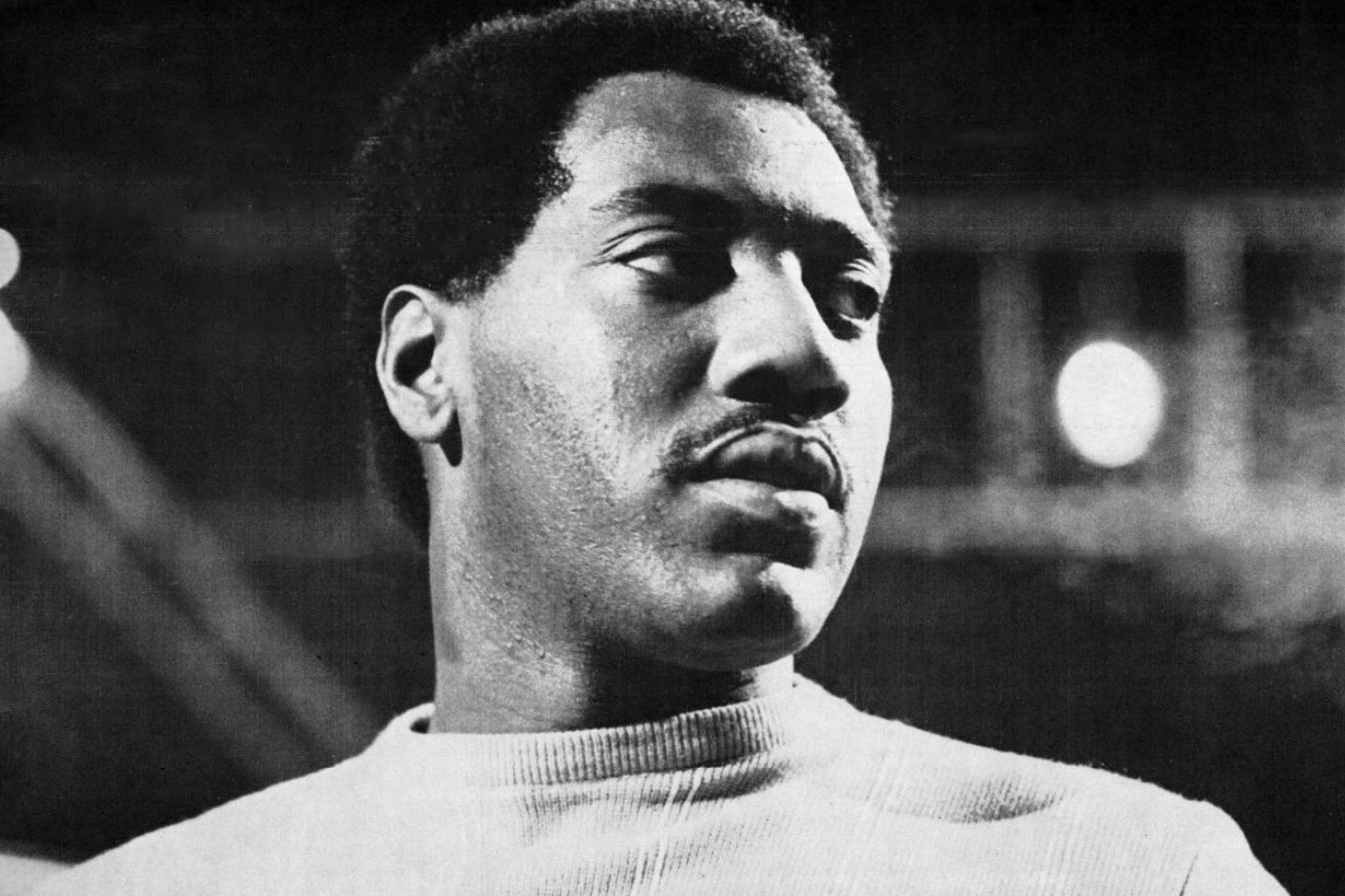 A black and white photo of Otis Redding, looking off-camera to the right, wearing a light sweater.