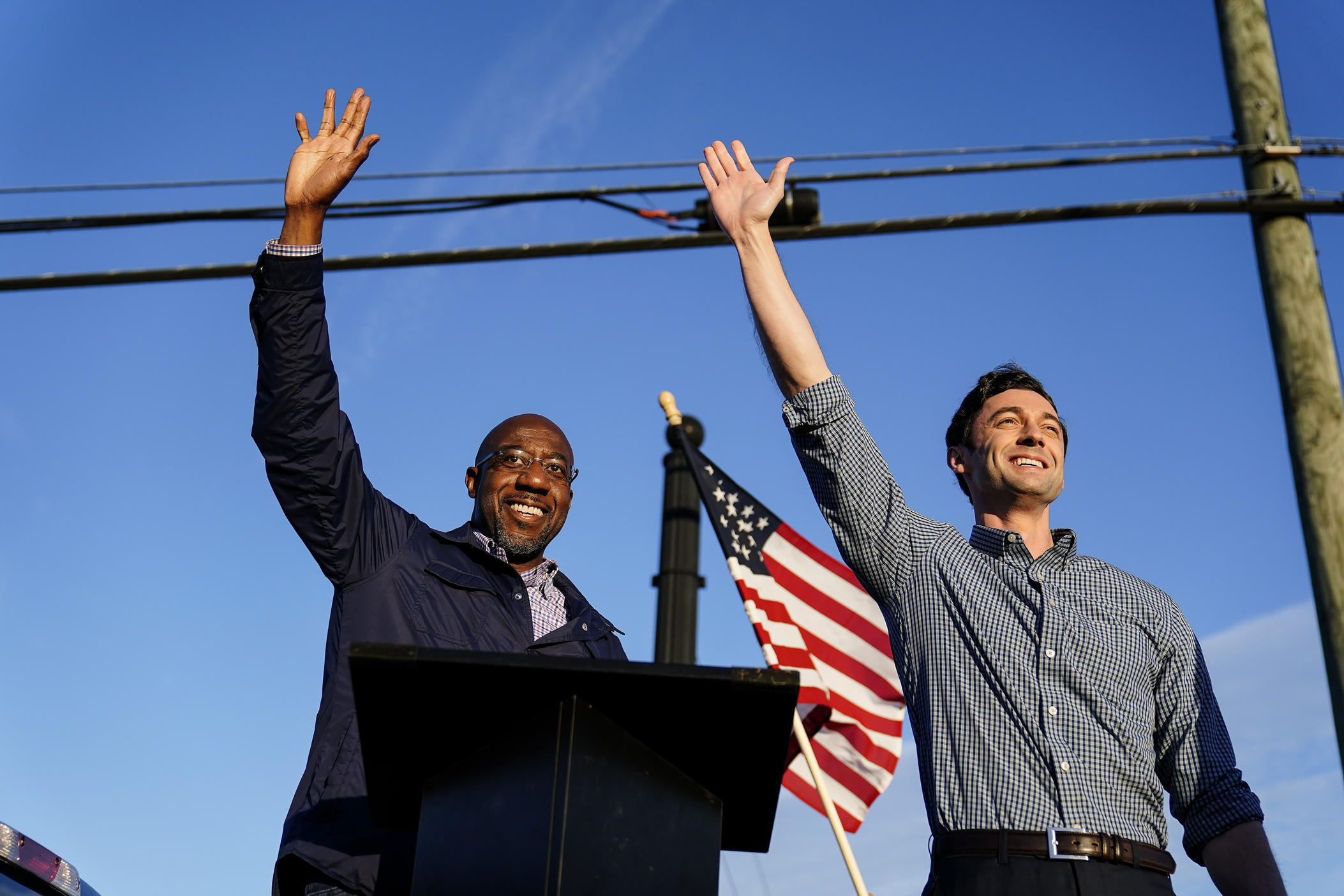Georgia Democrats Raphael Warnock, left, and Jon Ossoff, right, gesture toward a crowd during a campaign rally in Marietta, Ga in November 2020. The two won seats to the U.S. Senate in runoff races in January 2021.