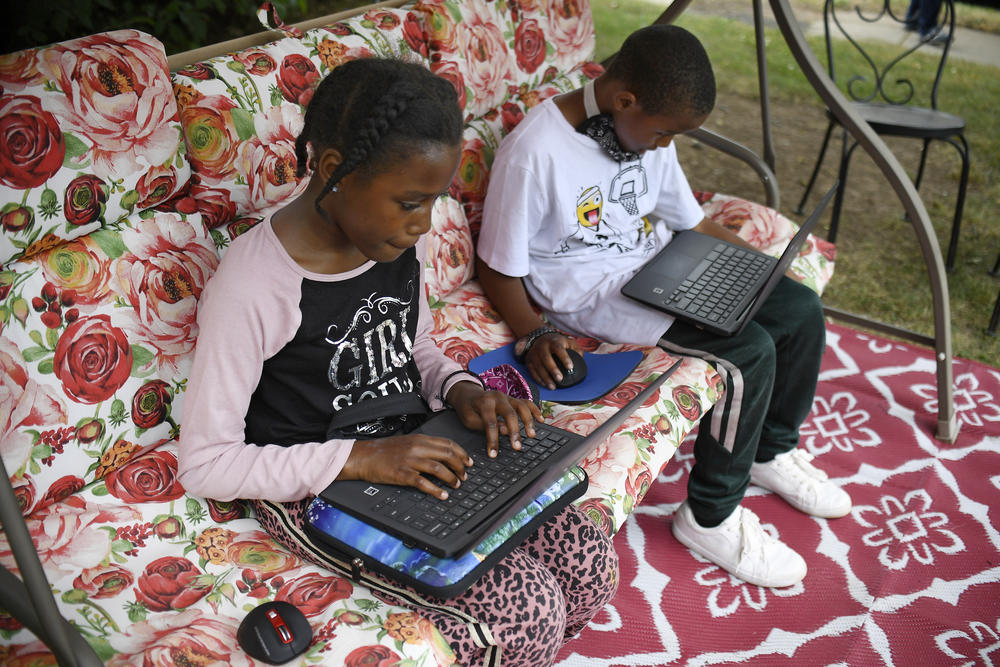 Two young children sit with laptops on a floral couch outside, doing schoolwork.