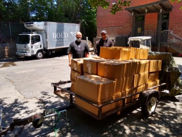 Employees from one of the Atlanta Community Kitchen Project's partners, Bold Catering & Design, stand by a ready-to-go shipment of prepared meals.