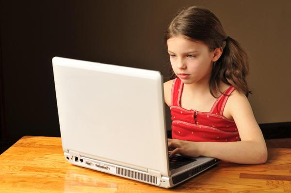 Girl sitting at computer.