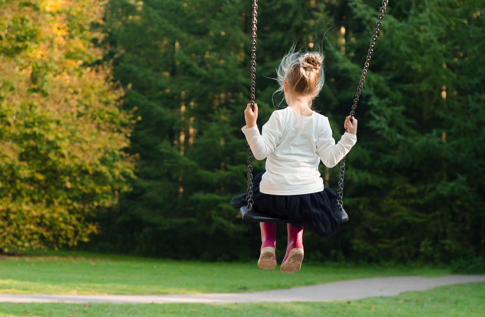 A child wearing pink rain boots uses a swing