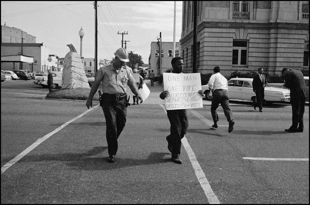 """John Lewis holding up a sign that reads """"One Man One Vote,"""" advocating for voting rights and voter registration for African Americans."""