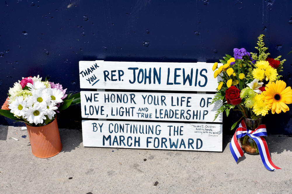 A sign placed at the base of a John Lewis mural in Atlanta.