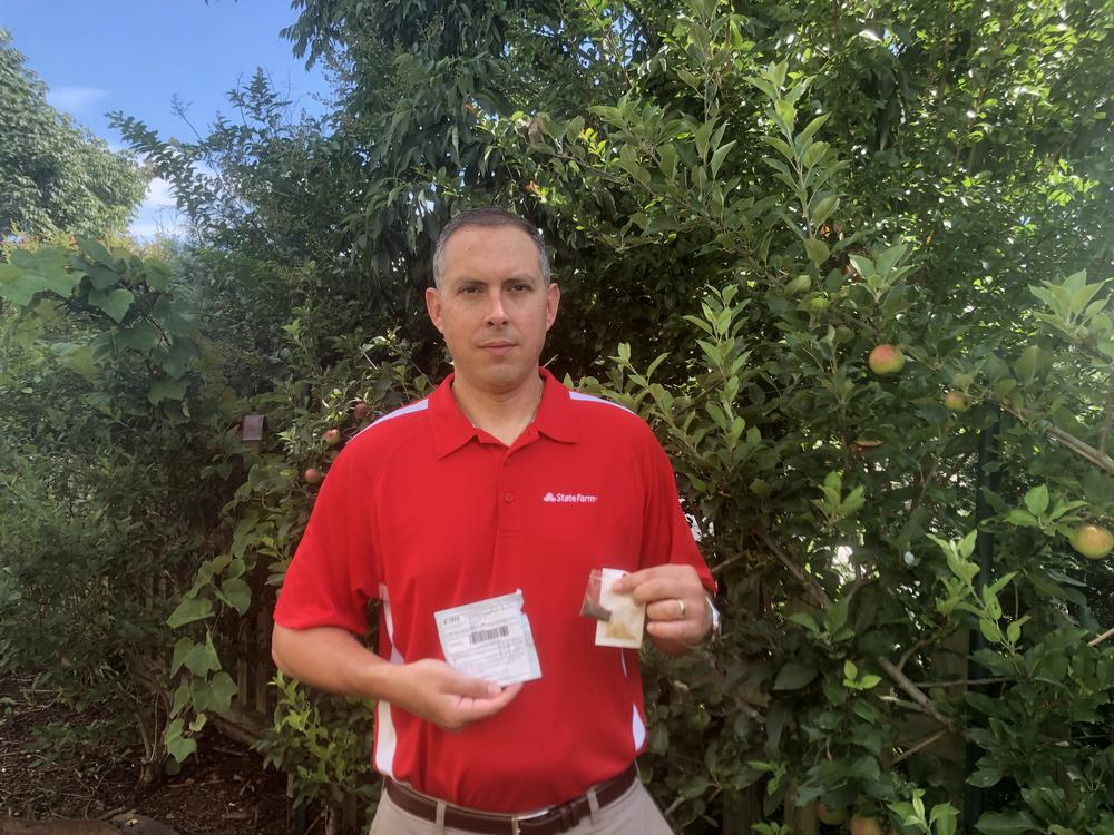Kirk Buchholz holds seeds mailed from China to his Woodstock home.