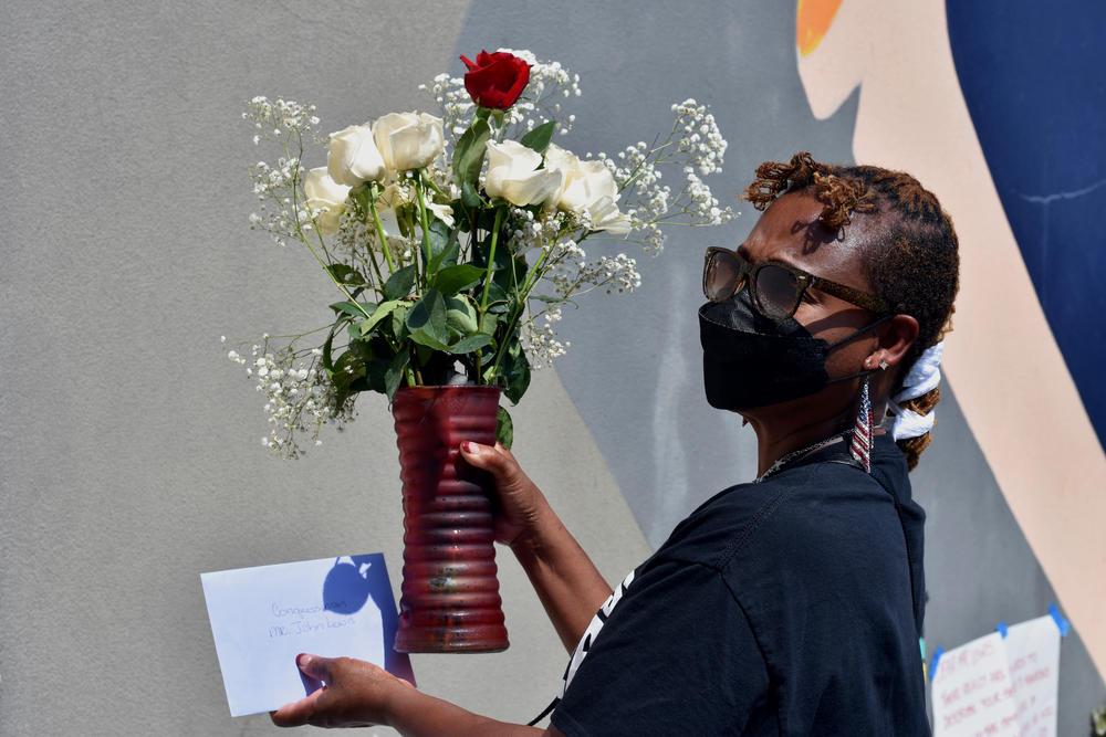 Phyllis Dent-Brown lays flowers down at the base of a John Lewis mural in Atlanta.