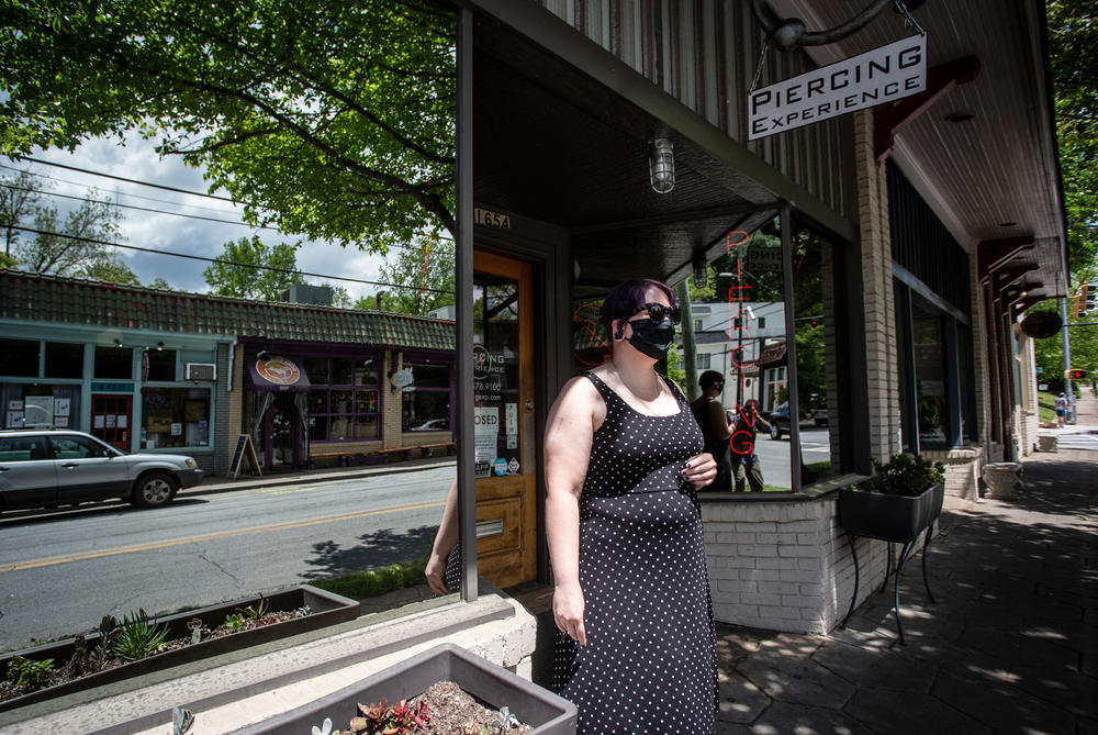 A masked women stands outside a business in Atlanta closed by the pandemic.