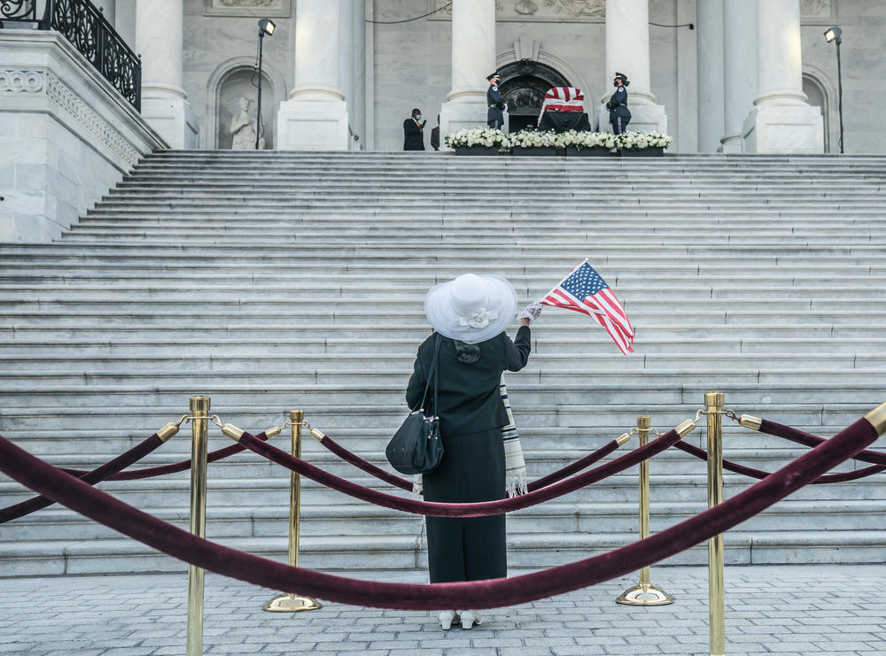 A woman waves an American Flag as she looks on at the casket of John Lewis outside the US Capitol