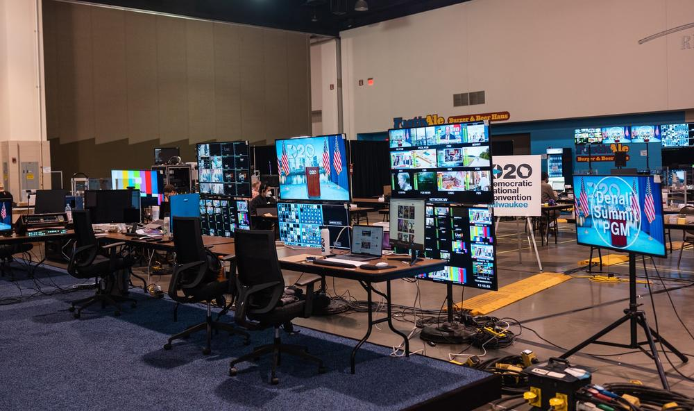 A behind the scenes look at the set-up for the Democratic National Convention. Television monitors are arrayed across the floor in front of several chairs and a desk.