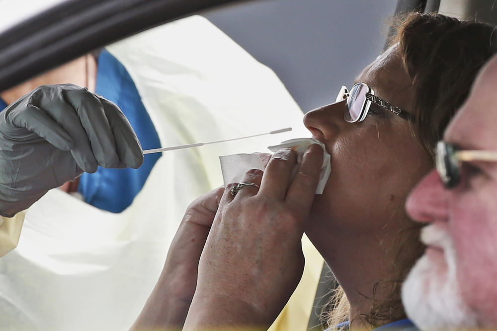 A woman in the passenger seat of a car is swabbed for a COVID-19 test at a mobile testing site.