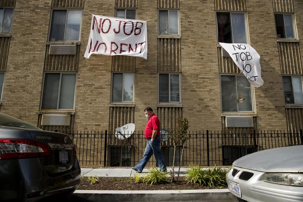 "Cloth signs that read ""No Job No Rent"" hang from the windows of an brown brick apartment building. In front of them, a man wearing jeans and a red shirt and a face mask walks on the sidewalk."