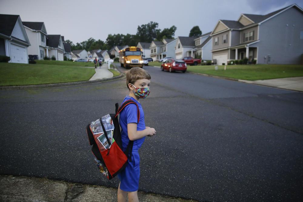 A student in Dallas, Georgia stands near a school bus.
