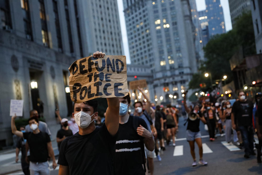 """A man at a protests holds a cardboard sign that reads, """"Defund the Police."""""""