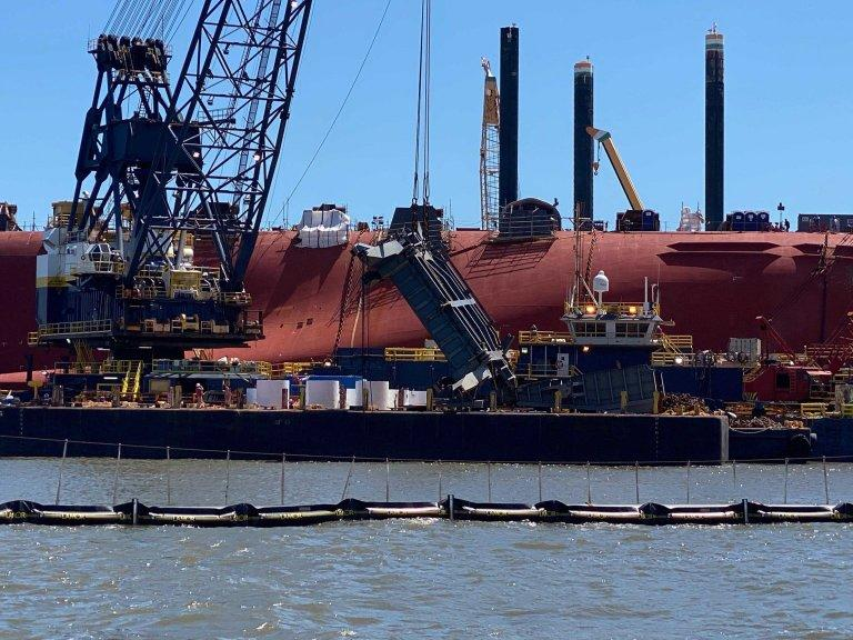 A salvage crew used a crane on June 24 to hoist a section of the Golden Ray's ramp used to load vehicles on and off the ship. The Coast Guard is delaying the ship's removal from St. Simons Sound until at least October to avoid the peak of hurricane season.