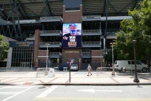 A digital image of Georgia Tech football coach Geoff Collins urges students walking by an entrance to Bobby Dodd Stadium to wear a mask.