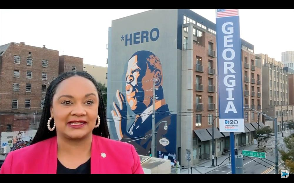 Georgia Democrat speaks to the Democratic National convention from aside a mural of Congressman John Lewis.