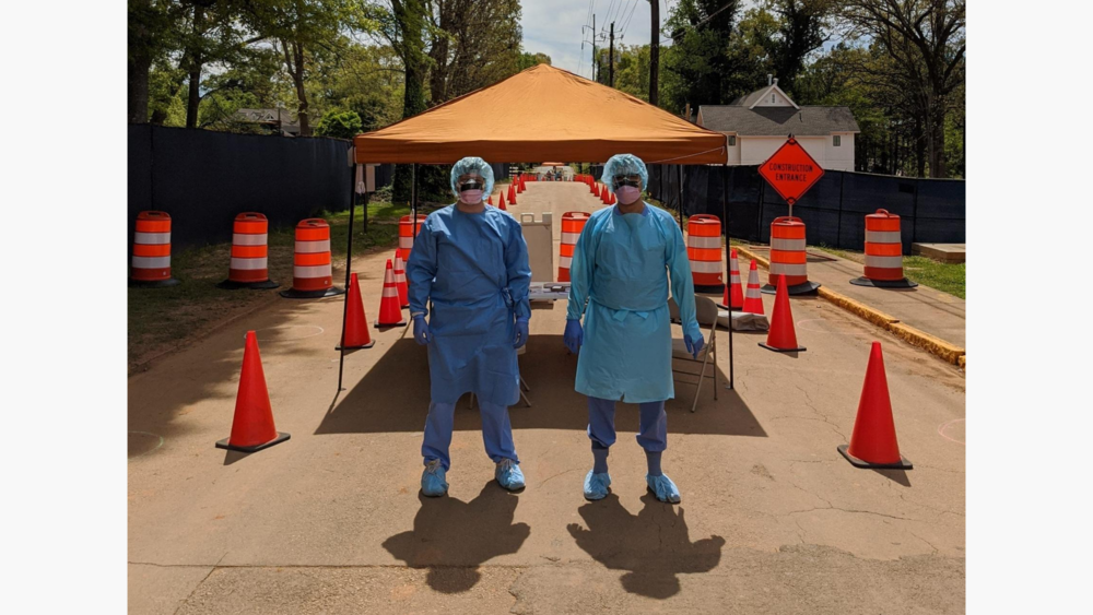 Two people are in the foreground with blue hairnets, blue medical scrubs, and a white mask looking at the camera. On the left and right, construction cones fade into the background. An orange medical aid tent station is behind them.