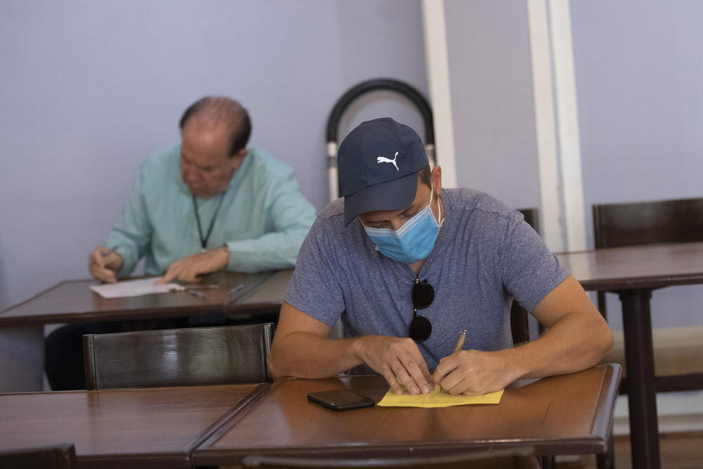 A voter wearing a mask writes on a piece of paper.