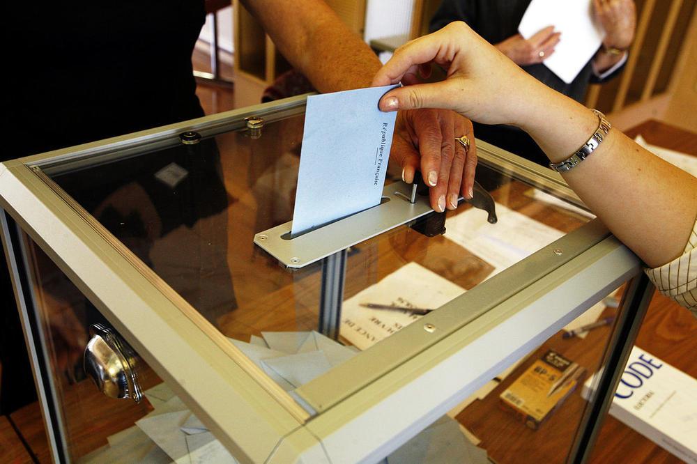 A ballot is dropped into a clear ballot box.