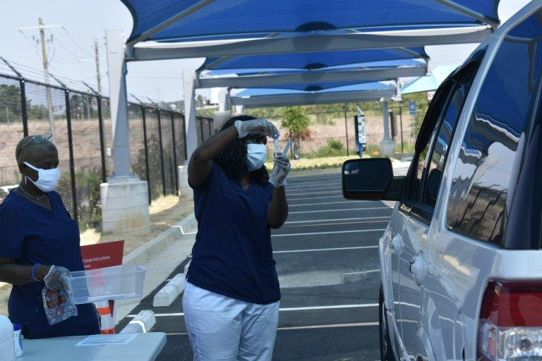 A public health worker collects a sample from someone at a mega testing site at Atlanta Hartsfield-Jackson Airport last month. The site will close Friday.