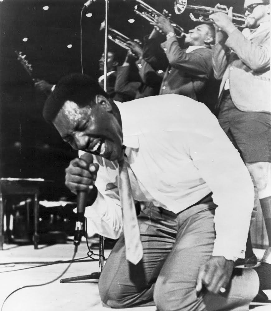 Otis Redding on his knees, singing into a microphone. Behind him, three men play trumpets.