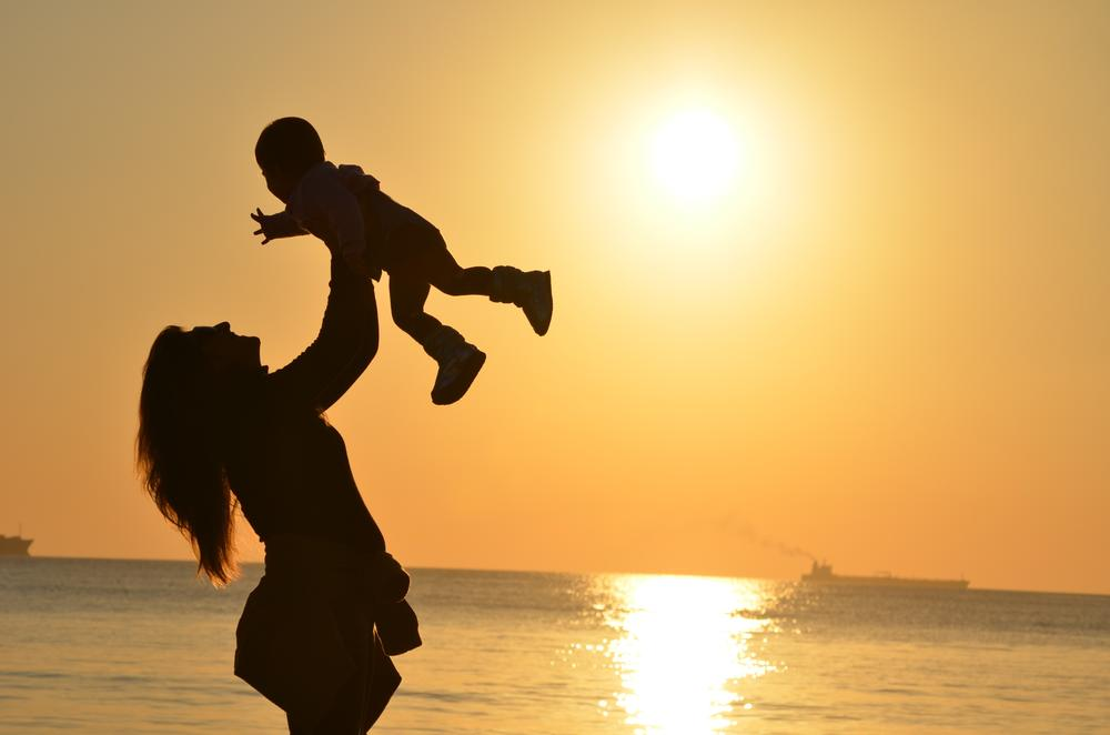 A person holds a toddler up on a beach