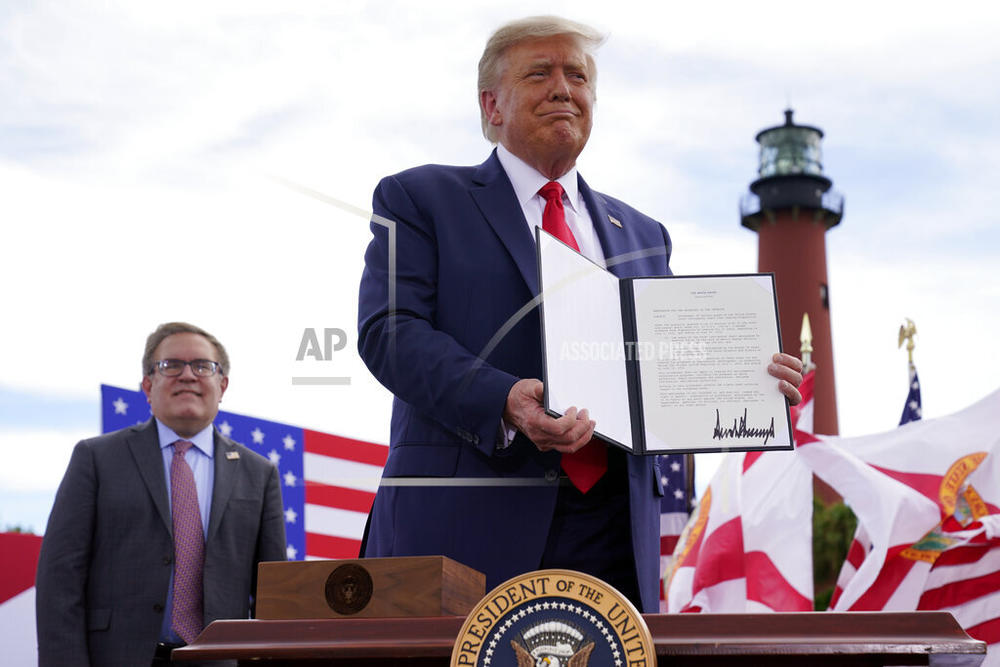 President Donald Trump holds a signed memorandum to expand the offshore drilling moratorium to Florida's Atlantic coast, Georgia and South Carolina after speaking at the Jupiter Inlet Lighthouse and Museum, Tuesday, Sept. 8, 2020, in Jupiter, Fla. At left is Environmental Protection Agency Administrator Andrew Wheeler.
