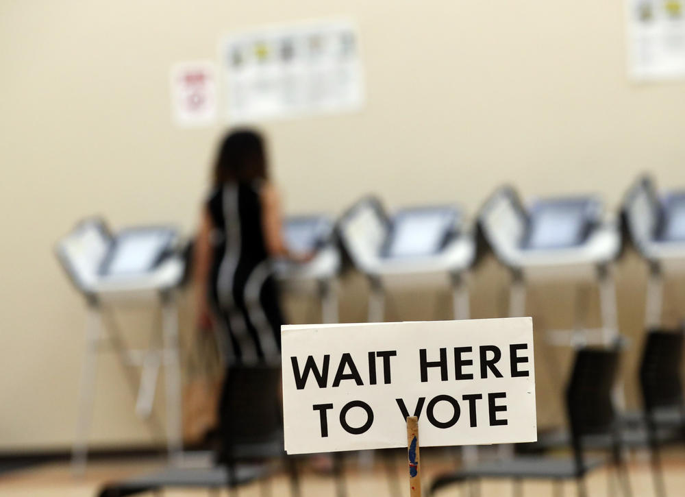 A sign tells voters to wait in line as they wait to vote.