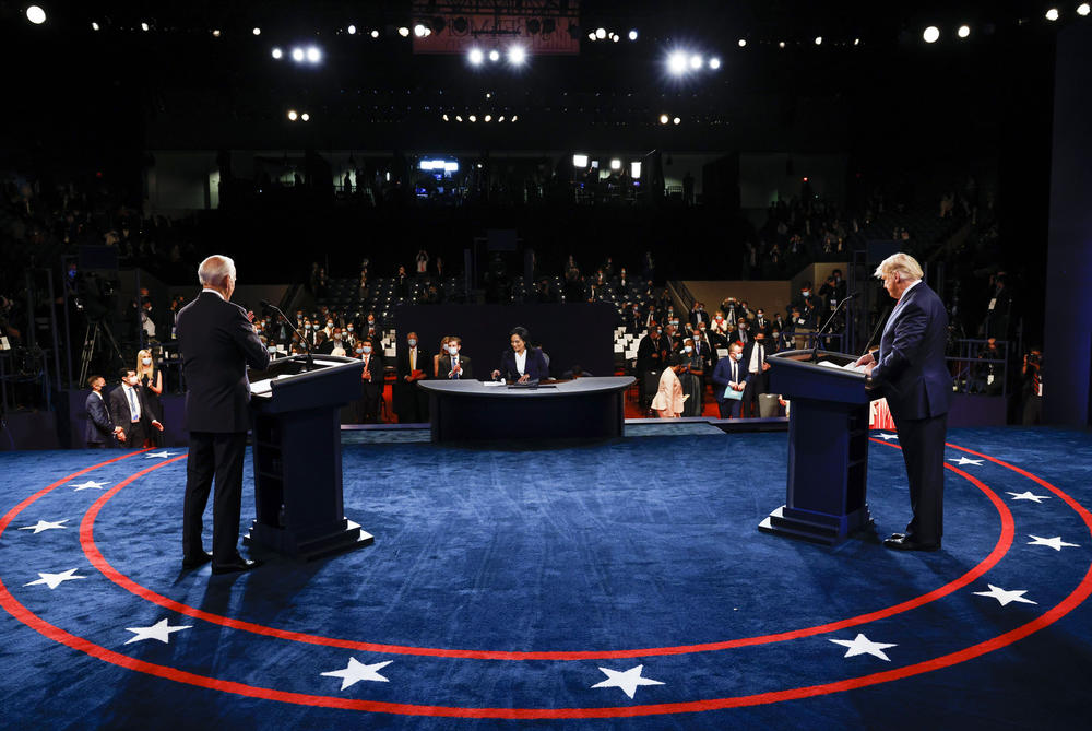 Joe Biden and Donald Trump stand on the debate stage.
