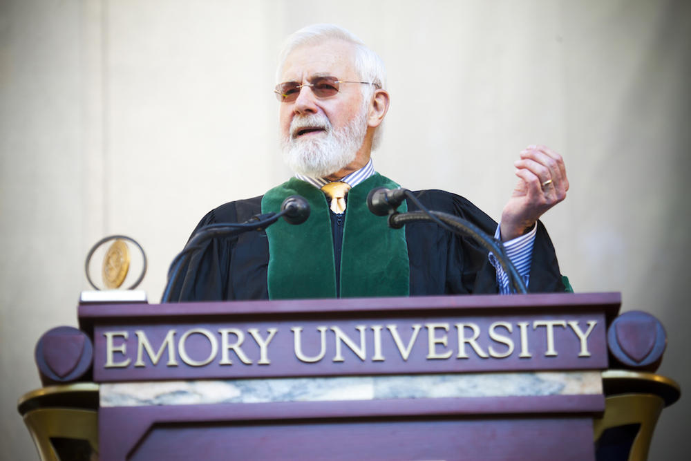 Doctor Bill Foege address a crowd from a fancy pulpit while wearing the collegiate gown.