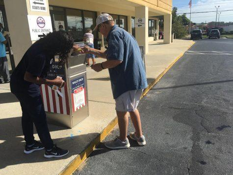 A poll worker assists a man with absentee ballots Friday at the Macon-Bibb County Board of Elections.