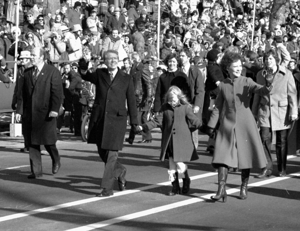 Jimmy and Rosalynn​ Carter hold hands of their da​ughter Amy, as they walk down ​Pennsylvania Avenue. Inauguration, January 20, 1977.