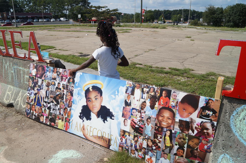 Malia Morton stands behind a collage paperboard.