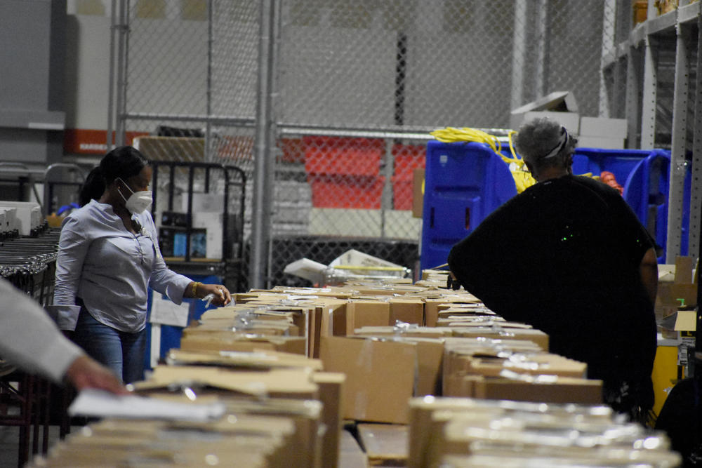 Workers sort through ballots in Fulton County's election warehouse.