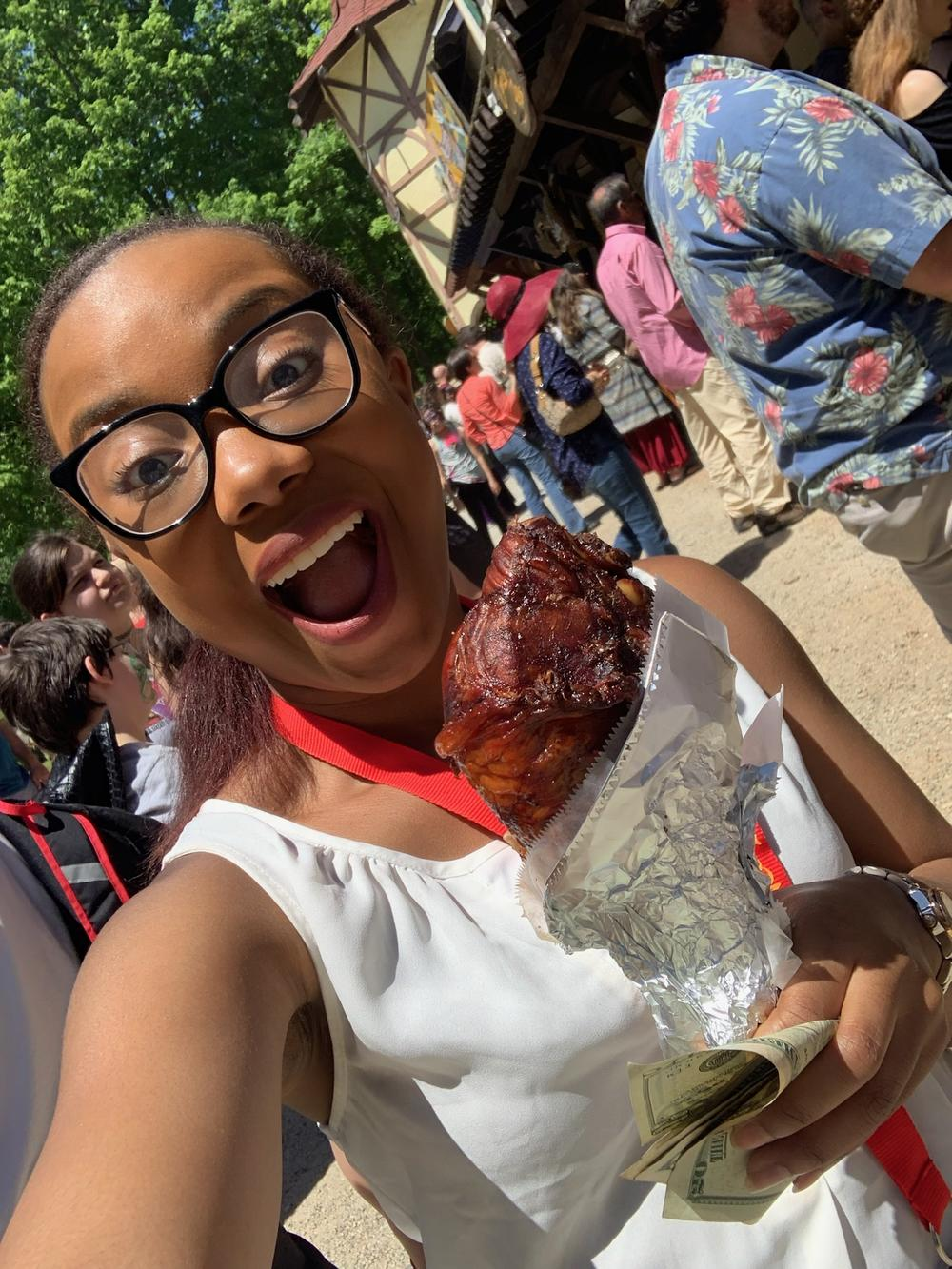 Madison McNair is smiling while holding a turkey leg at the ASL Day Festival in 2019.