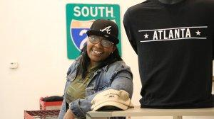 Chandra Moye poses for a photo in her store, Rock Steady Souvenirs and Gifts, in downtown Stone Mountain. The business owner says protests and counter protests have scared away customers and hurt the local economy.