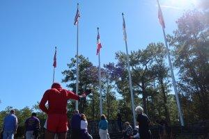 """Raphael J. Holland (in red), who lives in Atlanta, participates in a """"prayer for our park"""" event at Stone Mountain Park. Holland said he believes the Confederate flags should be removed from the park."""