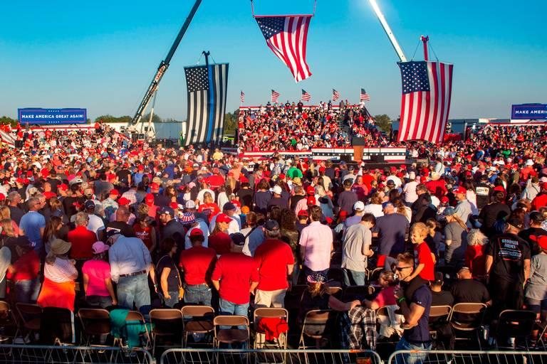 Attendants of President Donald Trump's Make America Great Again campaign rally cheer before his arrival at the Middle Georgia Regional Airport in Macon.