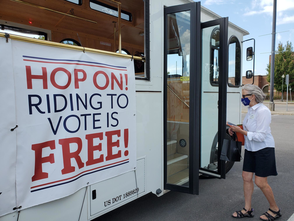 """Rebecca Rolfes boards a trolley that bears a banner announcing """"riding to vote is free"""""""