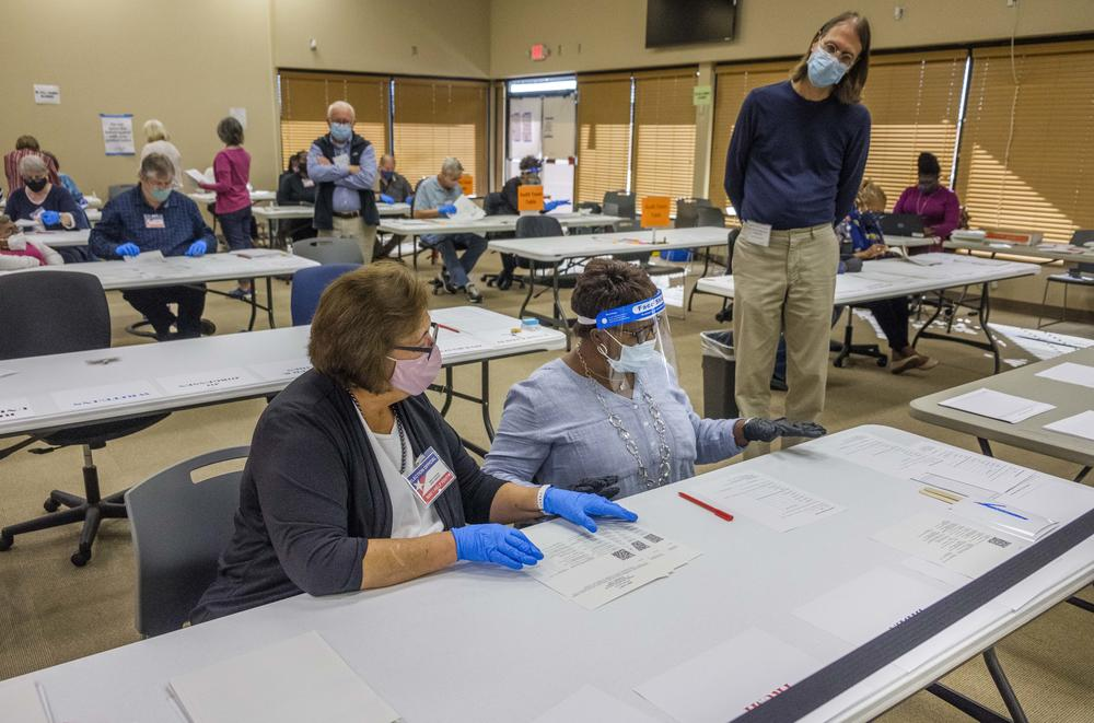 A poll watcher, right, and an auditing team, left, in the Bibb County Board of Elections in Macon on Monday, November 16.