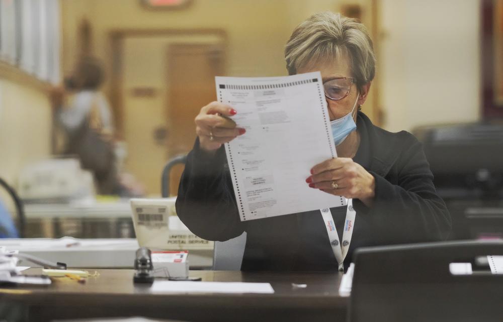 poll worker inspects absentee ballot