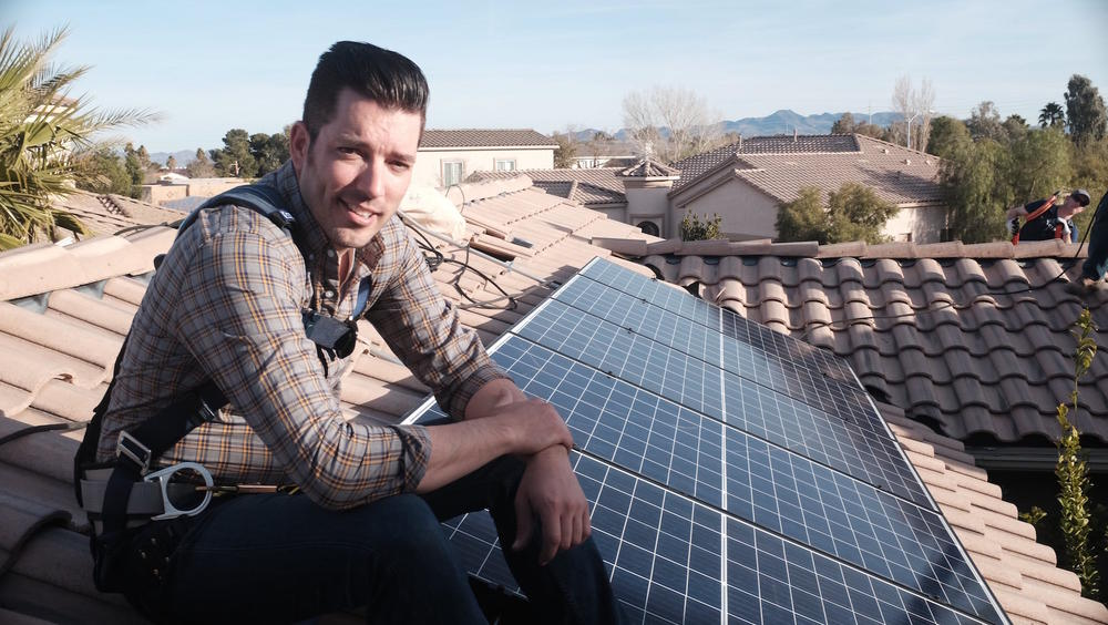 """""""Power Trip"""" director Jonathan Scott takes a break from installing solar panels on a rooftop."""