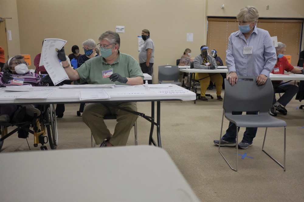 A Republican Party poll watcher keeps an eye on the recount in Macon Friday. There were two poll watchers for seven teams of auditors.