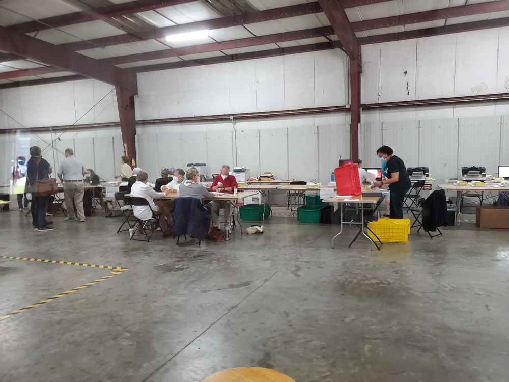 Ballots are counted at a series of tables inside of a large room in Savannah, Georgia.
