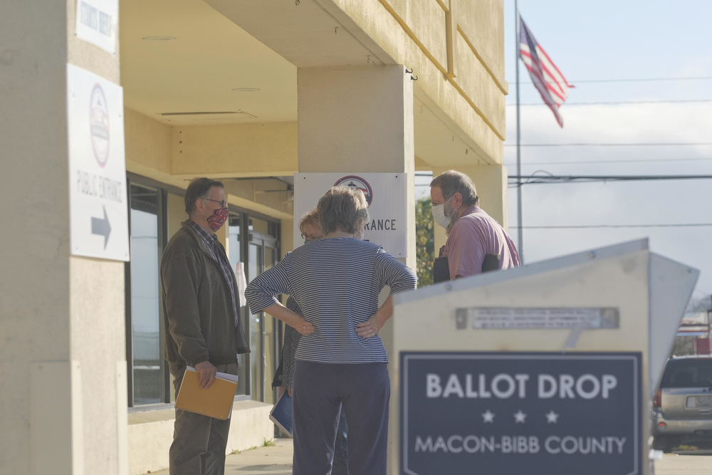 Poll watchers huddle in front of the Bibb County Board of Elections before the start of the Georgia risk-limiting audit of the presidential vote Friday.