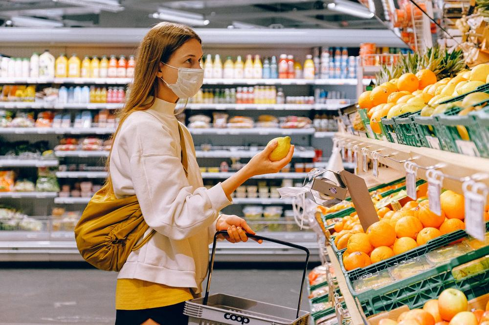 Woman grocery shopping in a mask