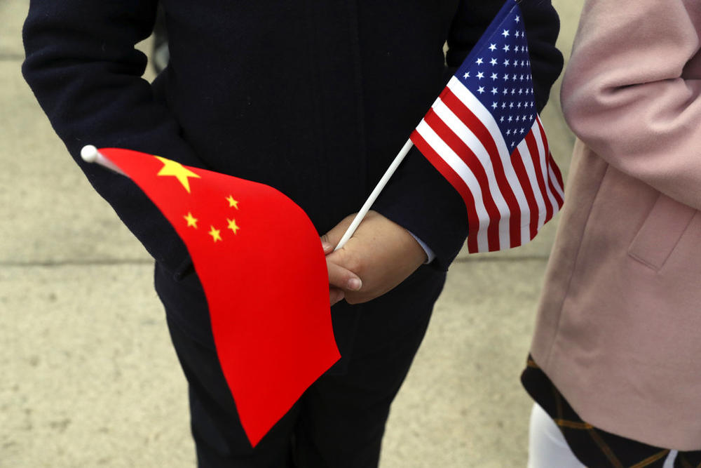 People hold Chinese and American flags as they wait for President Donald Trump and Chinese President Xi Jinping to participate in a welcome ceremony at the Great Hall of the People, Thursday, Nov. 9, 2017, in Beijing, China. (AP Photo/Andrew Harnik)
