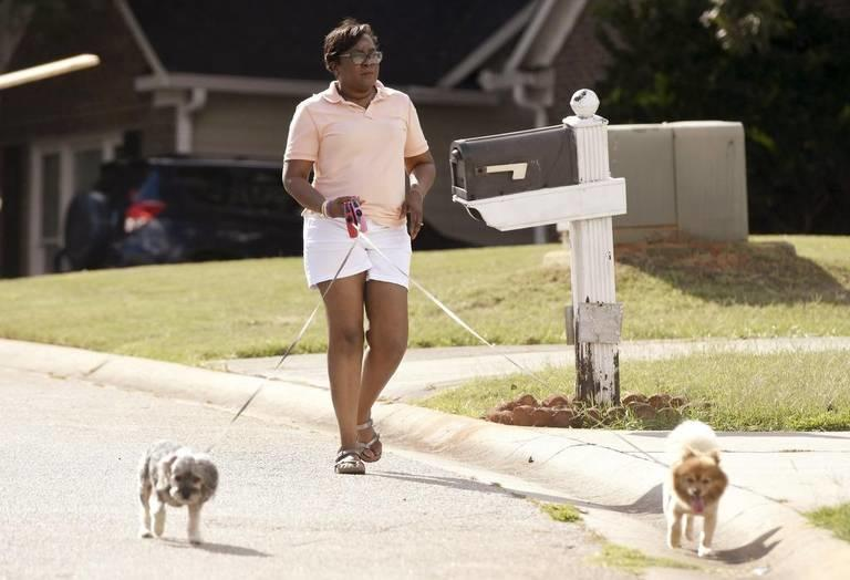 Arthena Caston walks her dogs around her neighborhood in North Macon. Caston, 54, has been diagnosed with early onset dementia.