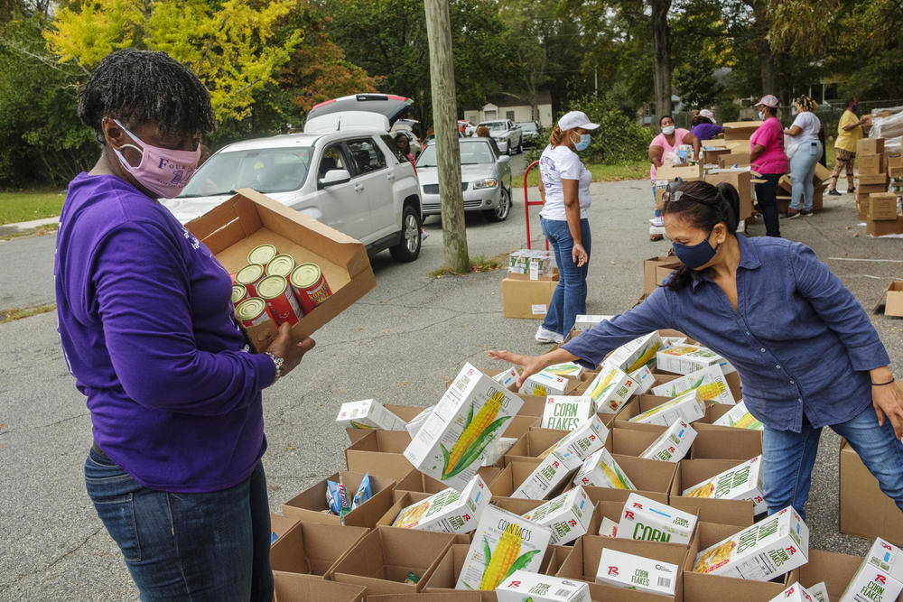 Volunteers, mostly from the Single Moms Connect support group, prepare grocery boxes during one of the group's twice monthly food disbursals in Houston County.